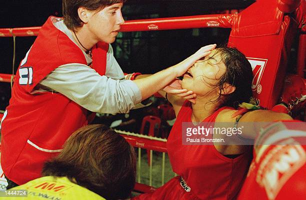 Irish kick boxer Niamh acts as 'corner man' giving the water and needed care between bouts to Muay Thai kick boxer Boonterm May 2000 at Rangsit...