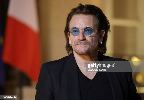 Irish lead singer of rock band U2 Paul David Hewson aka Bono delivers a statement in the courtyard of the Elysee Palace in Paris after a meeting with...