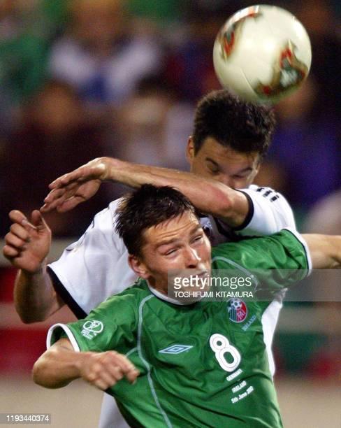 Irish midfielder Matt Holland and German midfielder Michael Ballack collide as they head the ball during the Group E first round match...