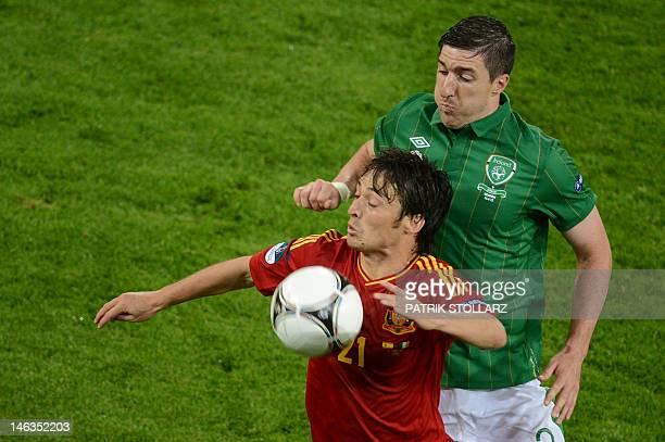 Irish midfielder Stephen Ward vies with Spanish midfielder David Silva during the Euro 2012 championships football match Spain vs Republic of Ireland...