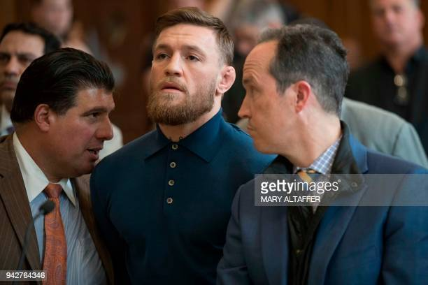 Irish Mixed Martial Arts fighter Conor McGregor looks on next to his lawyer Jim Walden and John Arlia during his arraignment at the Kings County...