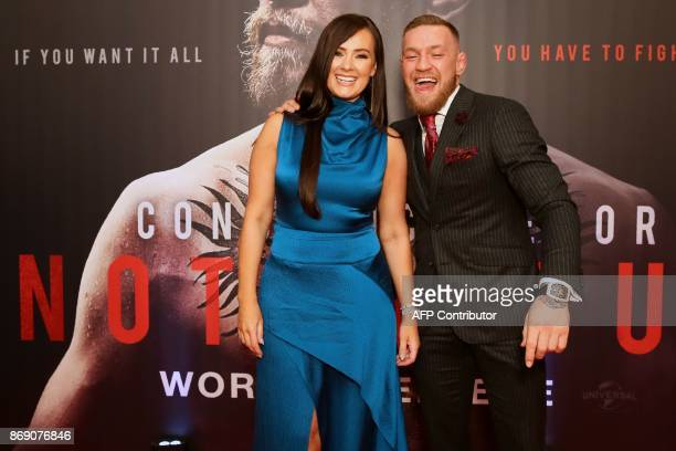 Irish mixed martial arts star Conor McGregor poses with his partner Dee upon arrival to attend the world premiere of the documentary film 'Conor...