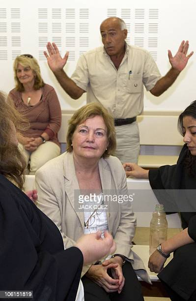 Irish Nobel laureate Mairead Maguire sits among lawyers as Israel's nuclear whistleblower Mordechai Vanunu gestures at the Petah Tikva District Court...
