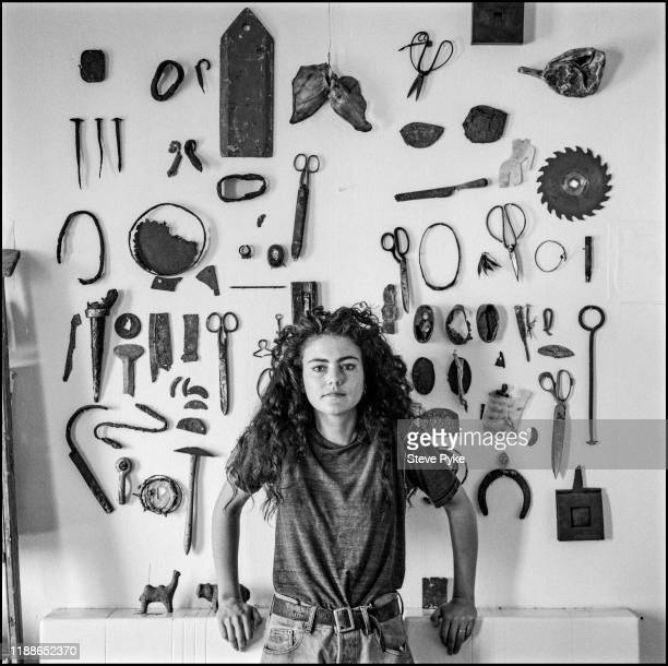 Irish painter Claire Carpenter in front of a collection of metal artefacts London 16th June 1994