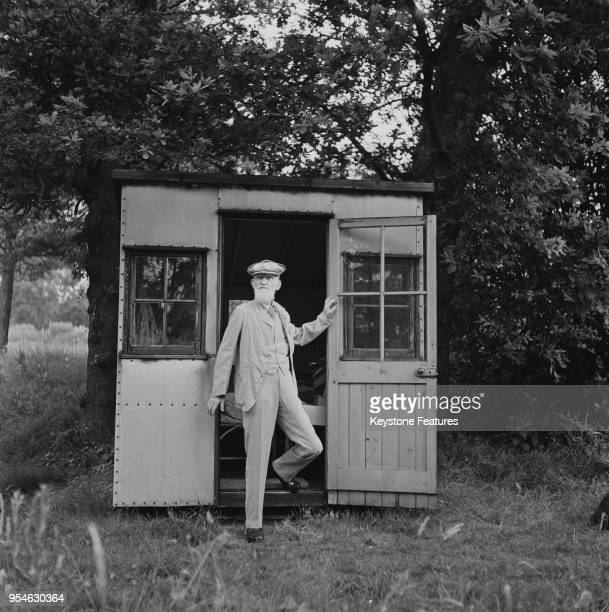 Irish playwright George Bernard Shaw emerges from his 'Retreat' a wooden shed in the garden of his home Shaw's Corner in Ayot St Lawrence...