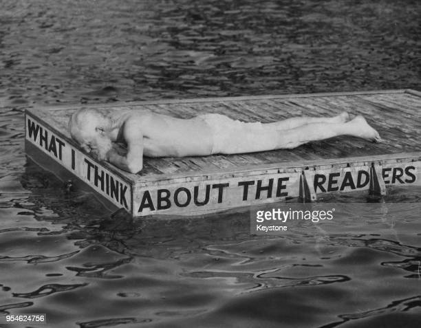 Irish playwright George Bernard Shaw lies on a swimming platform on which has been written 'What I Think About The Readers' 26th July 1949