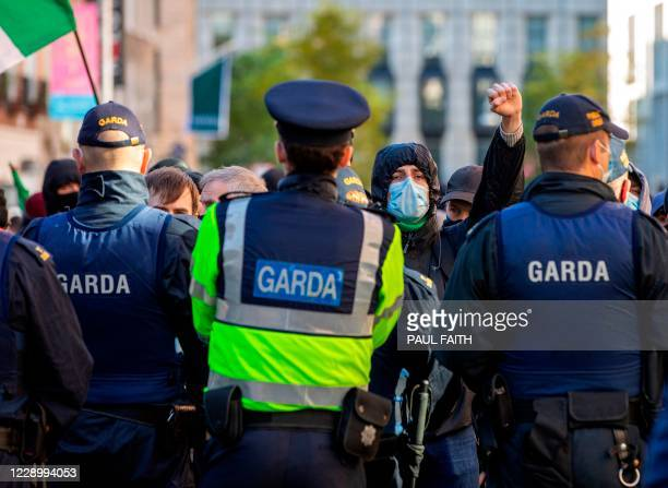 Irish police officers block counter-demonstrators as they attempt to disrupt a protest against the Irish government imposed restrictions put in place...