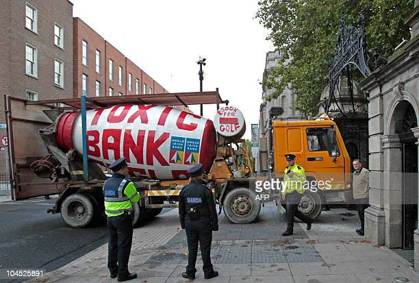Irish Police officers look at the cement mixer which was driven into the gate of Ireland's Parliament Building in Dublin on September 29 2010 Police...