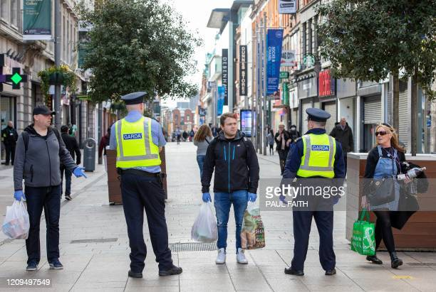 Irish police officers, or Garda officers, talk with members of the public as they conduct checks on pedestrians and motorists in Dublin city centre...