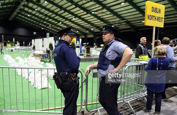 Irish police officers stand by as bags of counted ballot papers sit on the floor at the main general election count centre in Dublin Ireland on...