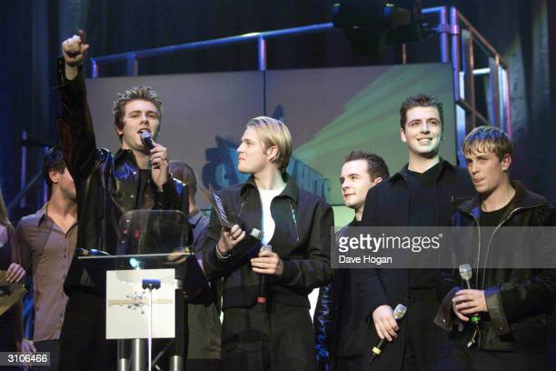 Irish pop stars Bryan McFadden Nicky Byrne Shane Filan Mark Feehily and Kian Egan of the pop group Westlife collect an award on stage at the TV Hits...