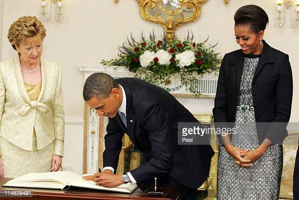 Irish President Mary McAleese and first lady Michelle Obama watch as U.S. President Barack Obama signs the visitor's book at Aras an Uachtarain, the...