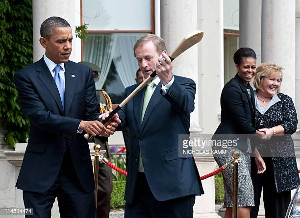 Irish Prime Minister Enda Kenny shows US President Barack Obama the use of a hurling stick as their wives Fionnuala Kenny and Michelle Obama look on...