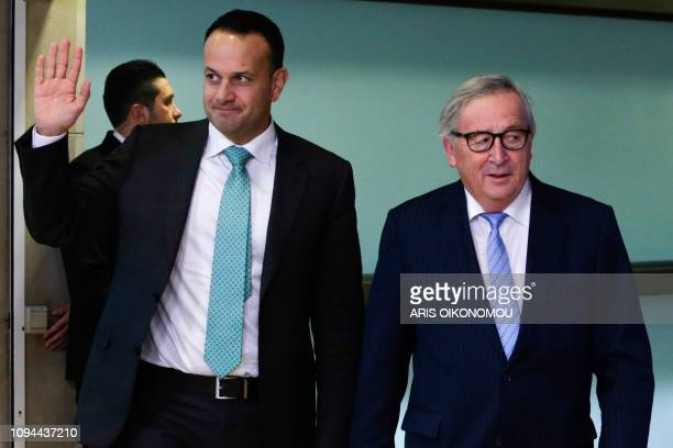 Irish Prime Minister Leo Varadkar waves as he walks past European Commission President JeanClaude Juncker at the European Commission headquarters in...