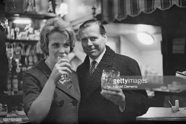 Irish producer and screenwriter Kevin McClory pictured with his wife Frederica Sigrist having a celebratory drink in a pub bar on 3rd December 1963...
