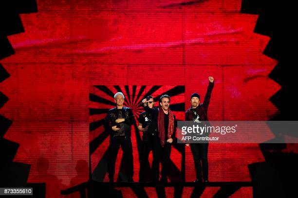 TOPSHOT Irish rock band U2 Bono The Edge Adam Clayton and Larry Mullen Jr accept the global icon award during the 2017 MTV Europe Music Awards at...