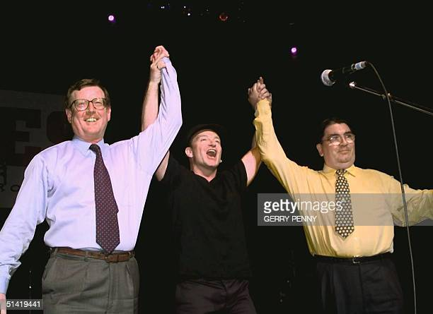 Irish rock band U2's lead singer Bono holds up the arms of Ulster Unionist leader David Trimble and SDLP leader John Hume on stage during a concert...
