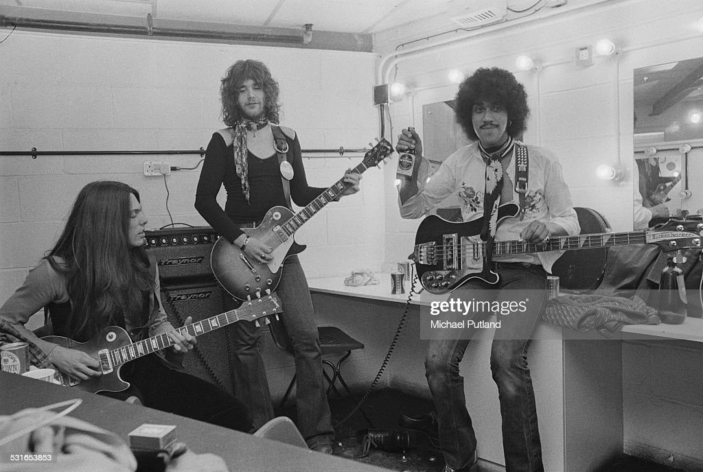 Irish rock group Thin Lizzy, rehearsing backstage in a dressing room at the Roundhouse, London, 3rd November 1974. Left to right: guitarist Scott Gorham, guitarist Brian Robertson and bassist/singer Phil Lynott (1949 - 1986).