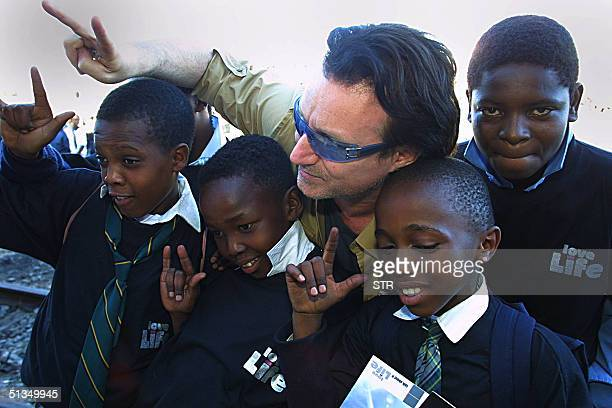 Irish rocker Bono, lead singer of U2 poses with school-children at the Love Life Train in Soweto township outside Johannesburg 24 May 2002. Bono was...
