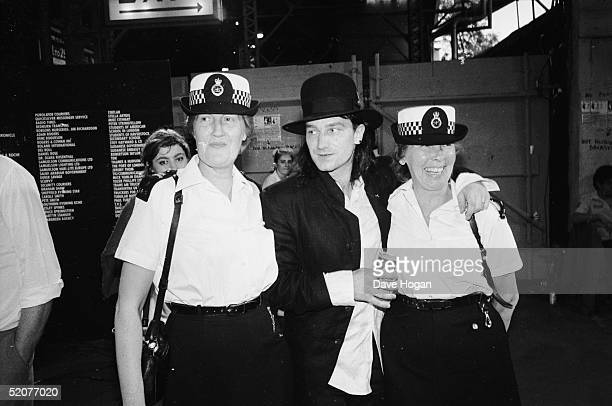 Irish singer Bono of U2 backstage with two policewomen at the Live Aid concert at Wembley Stadium London 13th July 1985