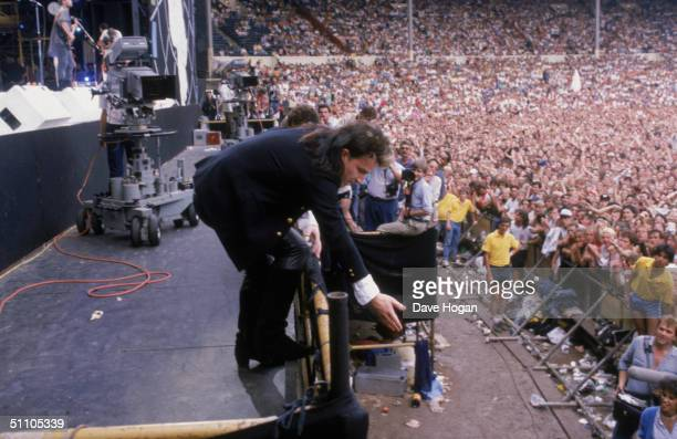 Irish singer Bono reaches down to an audience member during U2's performance at the Live Aid charity concert Wembley Stadium London 13th July 1985