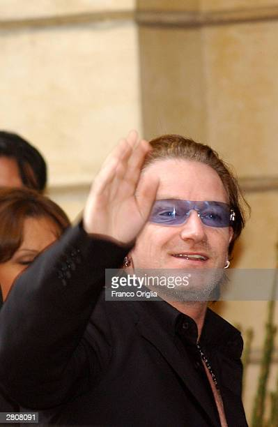 Irish Singer Bono waves as he leaves the Teatro Comunale at the end of the wedding of Luciano Pavarotti and Nicoletta Mantovani December 13 2003 in...
