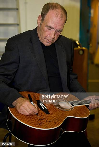 Irish singer Finbar Furey signs a guitar after taking part in a charity recording of a Children in Need album at Abbey Road studios in west London on...