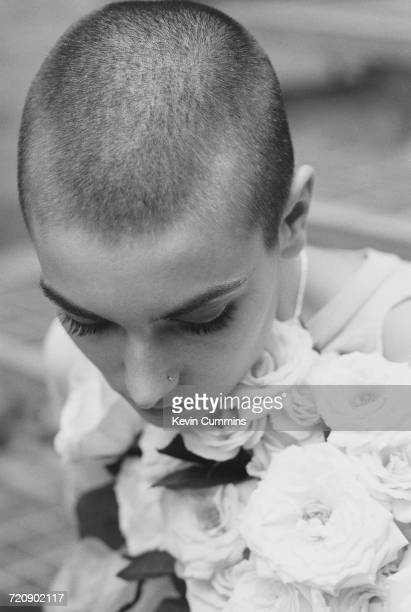 Irish singersongwriter Sinead O'Connor holding a bouquet of white roses 22nd October 1992