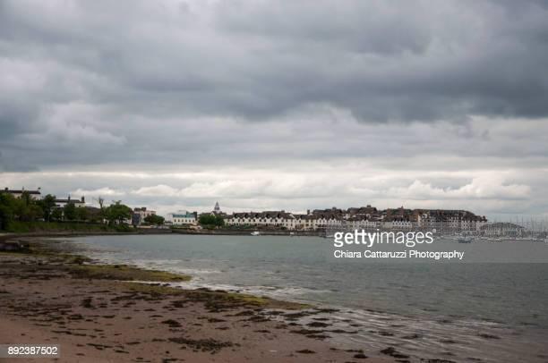 irish village and its sandy beach in a cloudy landscape - bedeckter himmel stock-fotos und bilder