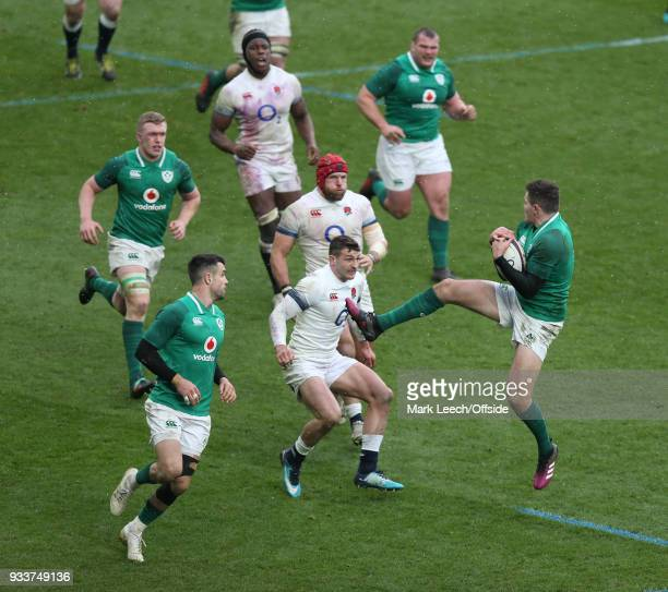 Irish winger Jacob Stockdale leaps to catch a high ball faced by Jonny May of England during the six nations rugby match between England and Ireland...