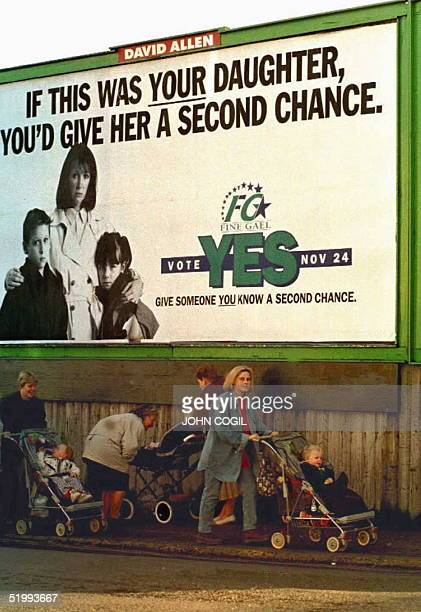 Irish women push strollers under a government-sponsored poster in Dublin, 13 November, as Ireland prepares for the 24 November referendum to end the...