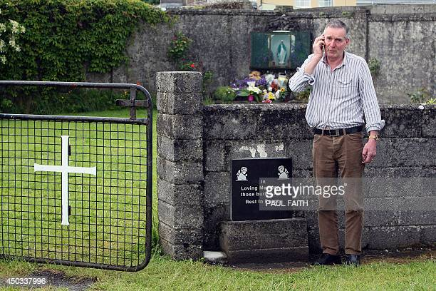 Irish writer John Pascal Rodgers speaks on his mobile phone as he stands beside a shrine in Tuam County Galway on June 9 erected in memory of up to...