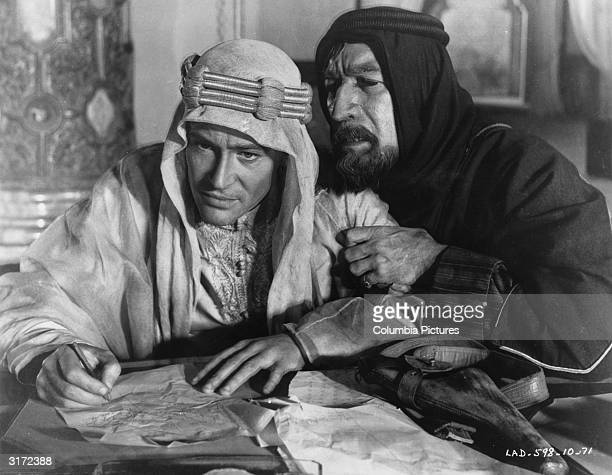 Irishborn actor Peter O'Toole and Mexicanborn actor Anthony Quinn sitting at a desk with O'Toole writing on a piece of paper in a still from director...