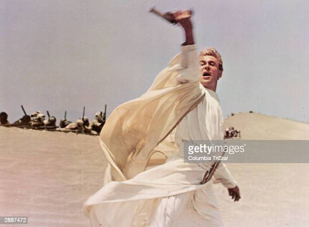 Irish-born actor Peter O'Toole waves his pistol while leading an army through the desert in a still from the film, 'Lawrence of Arabia,' directed by...