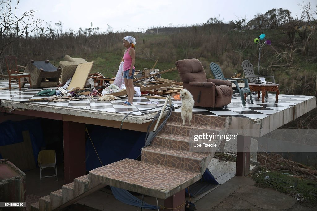 Irma Maldanado stands with Sussury her parrot and her dog in what is left of her home that was destroyed when Hurricane Maria passed through on September 27, 2017 in Corozal, Puerto Rico. Puerto Rico experienced widespread damage including most of the electrical, gas and water grid as well as agriculture after Hurricane Maria, a category 4 hurricane, passed through.