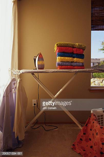 Iron and stack of towels on ironing board, with shirts hanging