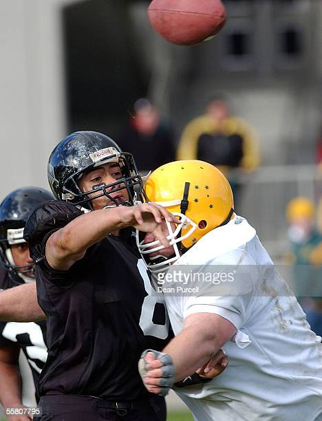 Iron Blacks Quarterback Joseph Toilolo gets the pass away before he is tackled during the American Football match between the New Zealand Iron Blacks...