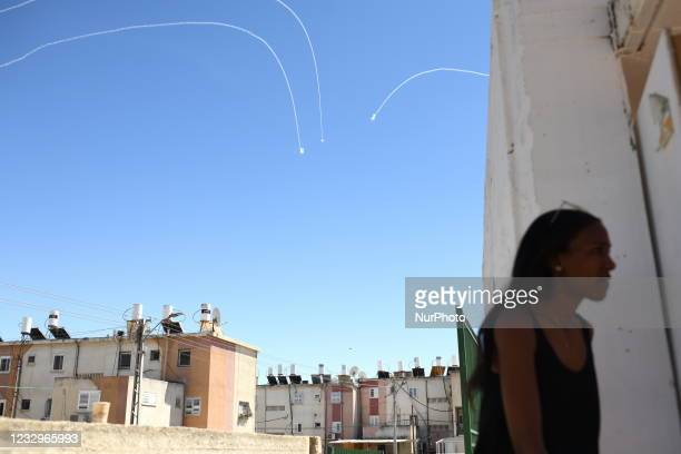 Iron Dome explosions are seen in sky above an Israeli woman as she is getting into a into a public bomb shelter, generaly used as synagogue, during a...