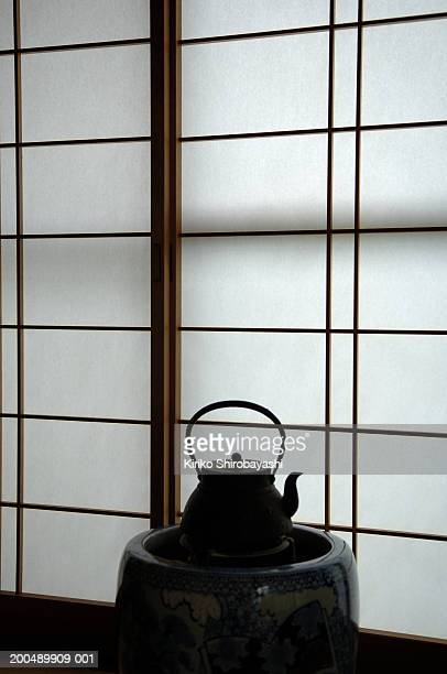 iron kettle on hibachi stove, paper screen in background - yonago stock photos and pictures