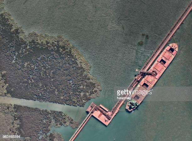 iron ore facility with ships - iron ore stock photos and pictures