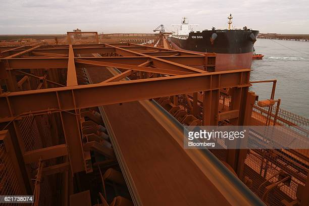 Iron ore travels along a shiploading conveyor as a bulk carrier sits moored at Fortescue Metals Group Ltd's Herb Elliott port facility in Port...