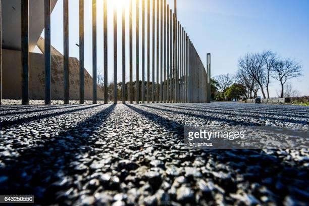 iron railing with shadow on asphalt ground - vedação de corrimão imagens e fotografias de stock