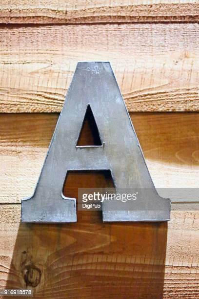 iron sheet 3d capital letter a on plank wall - letter a stock pictures, royalty-free photos & images