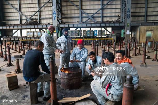 Iron workers enjoying the heat of a fire while taking a break
