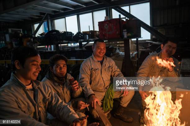 iron workers enjoying the heat of a fire while taking a break - south east asian ethnicity stock pictures, royalty-free photos & images