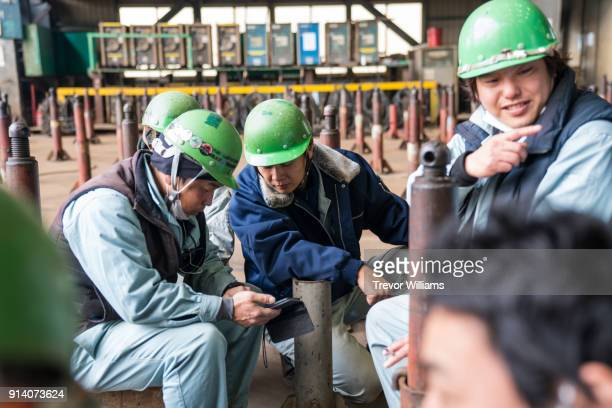 Iron workers looking at a smartphone during a break from work at a shipbuilding factory