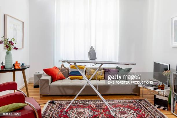 Ironing board in cool apartment living room.