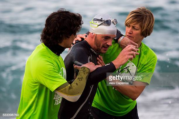 Ironman team members help an athlete as he exits the water after completing the swim leg of Ironman 703 Barcelona race on May 22 2016 in Barcelona...