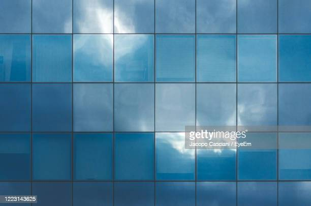 irregular clouds and sky reflections on textured blue glass - irregular texturizado stock pictures, royalty-free photos & images