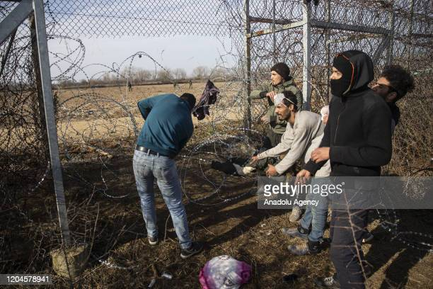 Irregular migrants cut down the iron wires as they continue to wait at the Pazarkule Border Gate in Karaagac neighbourhood in Edirne, Turkey to reach...